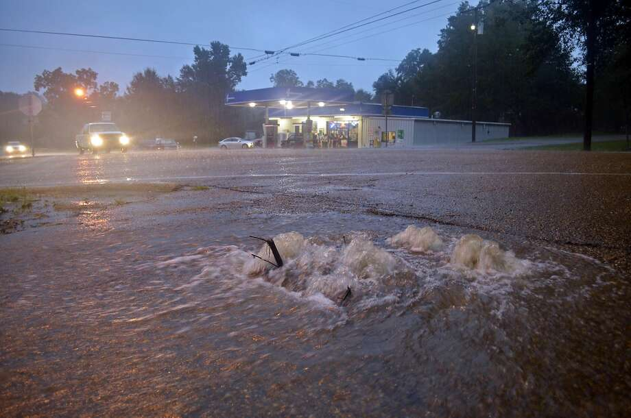 Floodwaters surge from a crack in a parking lot in Osyka, Miss. Numerous rivers in Louisiana and southern Mississippi were overflowing their banks following heavy rains across the region. Photo: Matt Williamson, Associated Press