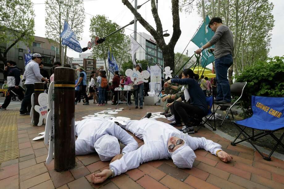 Members of Banolim, an advocacy group for workers in the electronic industry, perform during a rally against the Samsung's response to the former company employees' health problems. South Korea plans to review if there was any negligence in the government's handling of sick workers' inquiries about workplace toxins. An Associated Press investigation found the government repeatedly withheld such information following requests from Samsung. Photo: Ahn Young-joon /Associated Press / Copyright 2016 The Associated Press. All rights reserved. This material may not be published, broadcast, rewritten or redistribu