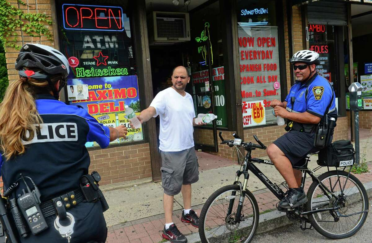 Norwalk police officers, Cristina Capela and Hector Delgado, who are part of the Norwalk Police Department bicycle unit in Norwalk, Conn., chat with owner of Maximo Deli and Grocery, Pedro Criollo, Thursday, August 11, 2016.