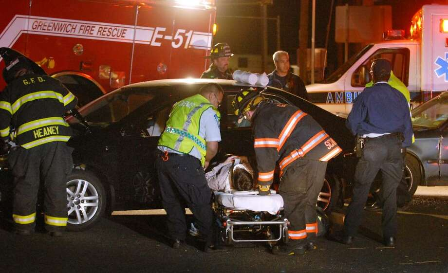 Greenwich emergencey personnel attend to the victim of a car accident on East Putnam Avenue and Havemeyer Lane, Greenwich, Thursday night, April 29, 2010. Photo: Bob Luckey / Greenwich Time