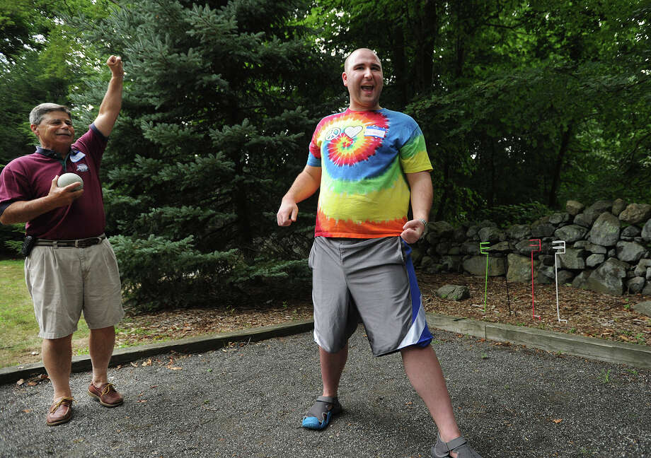 Wilton YMCA Special Olympics bocce team member Michael Shukovsky, right, of Wilton, celebrates a winning throw with the encouragement of coach Bob Genuario, left, during the team's practice at the home of fellow coach and state representative Larry Cafero in Norwalk, Conn. on Monday, August 1, 2016. Photo: Brian A. Pounds / Hearst Connecticut Media / Connecticut Post