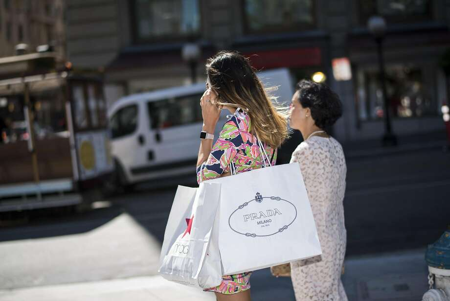 A shopper carries Macy's Inc. and Prada SpA bags while talking on a smartphone in San Francisco, California, U.S., on Wednesday, Aug. 10, 2016. The U.S. Census Bureau is scheduled to release retail sales figures on Aug. 12. Photographer: David Paul Morris/Bloomberg Photo: David Paul Morris, Bloomberg