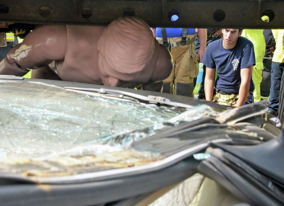 Rexford firefighter Fred Pedinotti, right, looks at a crash dummy pinned under a tractor trailer during hands on training in heavy vehicle lifting & stabilization during the 144th Annual Convention of the Firemen's Association of the State of NY Friday, Aug. 12, 2016, in Colonie, N.Y. (John Carl D'Annibale / Times Union)