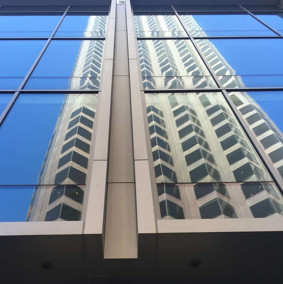 The iconic 555 California St., still known to many people as the Bank of America Building, as reflecting in its new neighbor 500 Pine St. Photo: The Chronicle, John King