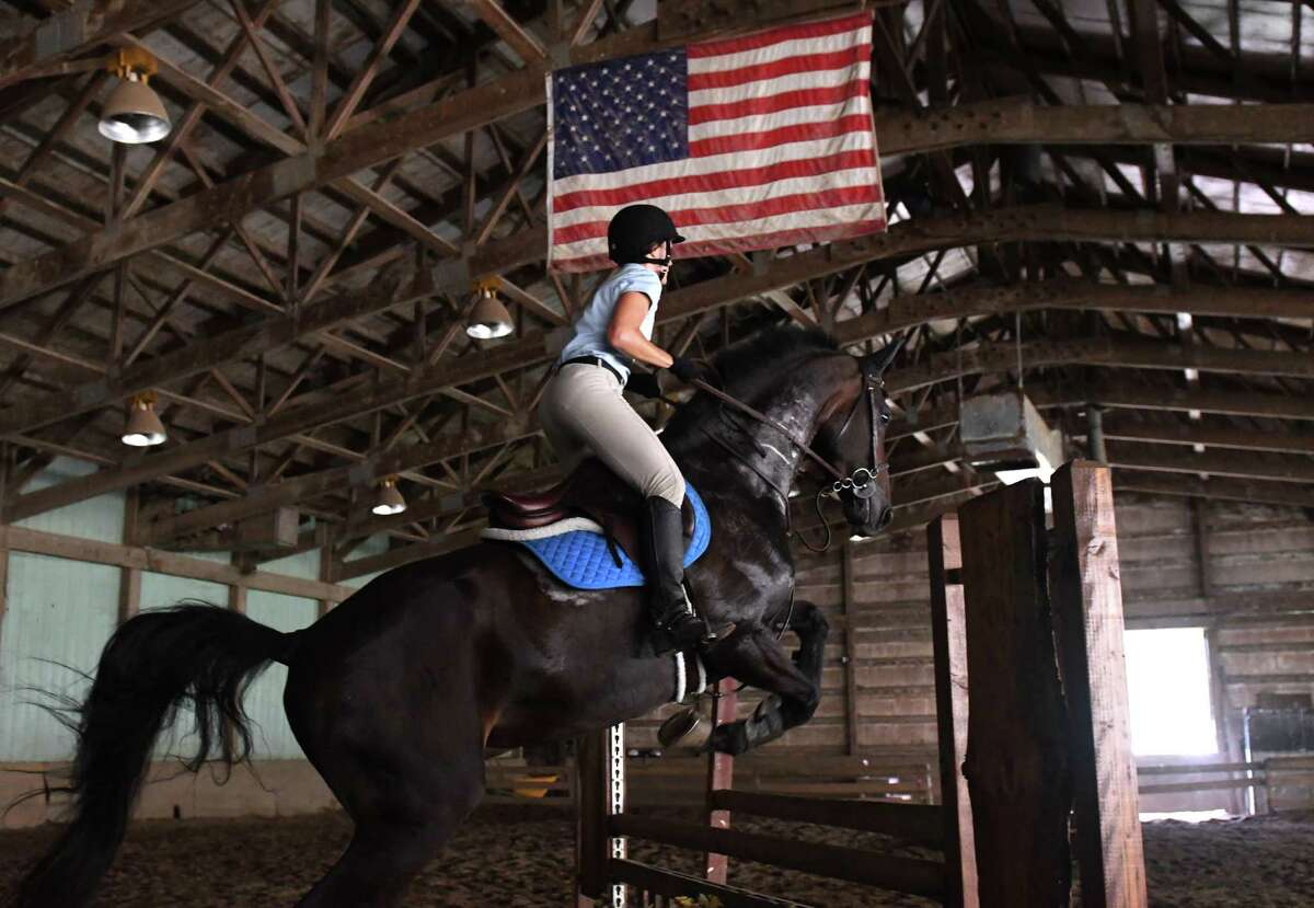 Theresa Lang of Ballston Spa makes a jump aboard Game Changer in the Dutch Manor Stables indoor ring on Friday, Aug. 12, 2016, in Guilderland, N.Y. The horse is owned by Julie Hoskinson. (Will Waldron/Times Union)