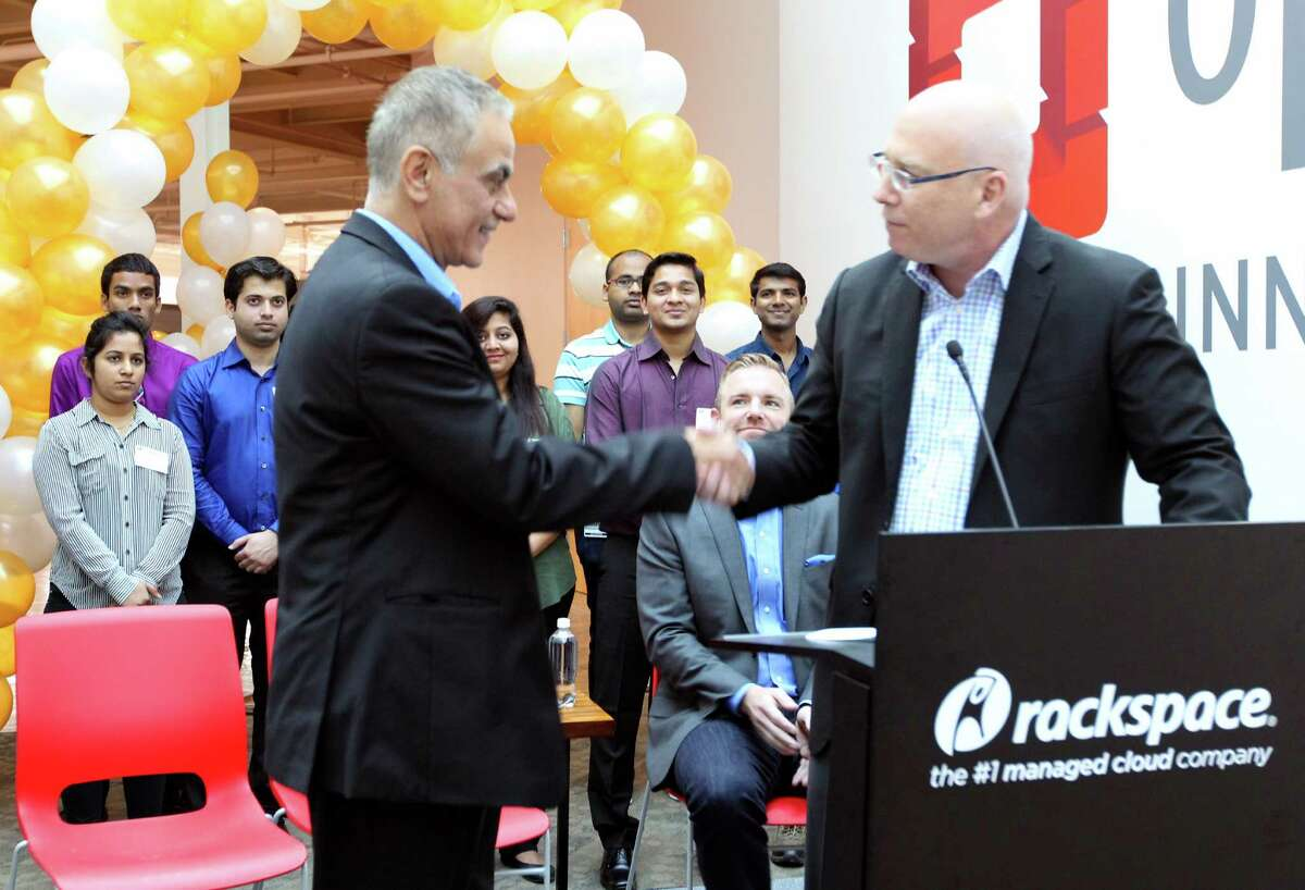 Imad Sousou, vice president of Intel's Software & Services Group, left, shakes hands with with Scott Crenshaw, senior vice president of product and strategy at Rackspace during a ribbon cutting ceremony announcing the opening of the OpenStack Innovation Center at Rackspace's San Antonio headquarters.