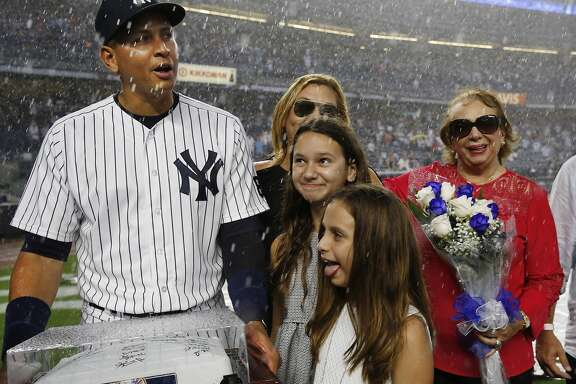 New York Yankees designated hitter Alex Rodriguez reacts to a sudden thunderstorm, while joined by his two daughters, mother, and another family member after he was presented with a signed base before his final game as a player, against the Tampa Bay Rays at Yankee Stadium in New York, Friday, Aug. 12, 2016. (AP Photo/Kathy Willens)