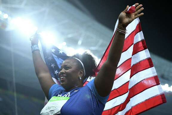 TOPSHOT - The USA's Michelle Carter carries the US national flag after the Women's Shot Put Final  athletics event at the Rio 2016 Olympic Games at the Olympic Stadium in Rio de Janeiro on August 12, 2016.   / AFP PHOTO / Johannes EISELEJOHANNES EISELE/AFP/Getty Images