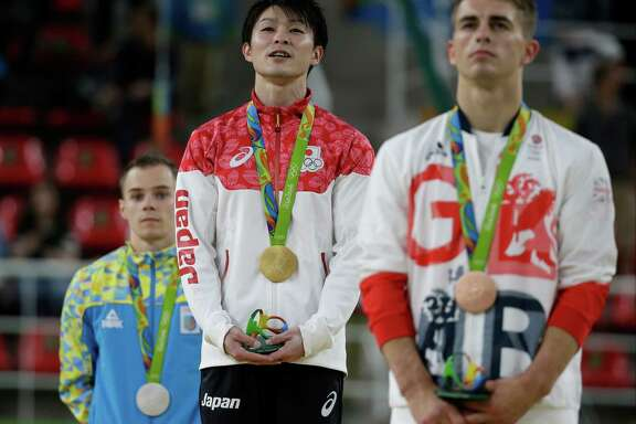 Gold medal winner Japan's Kohei Uchimura sings his national anthem flanked by silver medal winner Ukraine's Oleg Verniaiev, left, and Britain's Max Whitlock, bronze right, during the artistic gymnastics men's individual all-around final at the 2016 Summer Olympics in Rio de Janeiro, Brazil, Wednesday, Aug. 10, 2016. (AP Photo/Rebecca Blackwell)