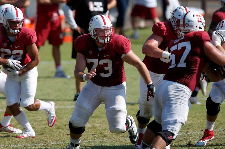 Center Jesse Burkett (73) creates open space for a running back during a Stanford Cardinal football practice in Stanford, Calif. on Saturday, Aug. 13, 2016.