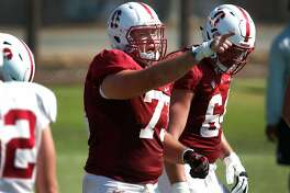 Center Jesse Burkett (73) directs the offensive line during a Stanford Cardinal football practice in Stanford, Calif. on Saturday, Aug. 13, 2016.