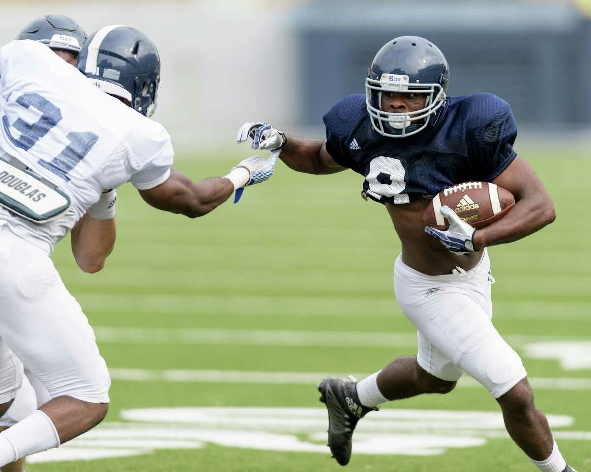 Darrion Pollard (8) 0f the Rice Owls attempts to avoid Martin Nwakamma (31) on a run around right end in an inter squad scrimmage on Saturday, August 13, 2016 at Rice Stadium in Houston Texas.