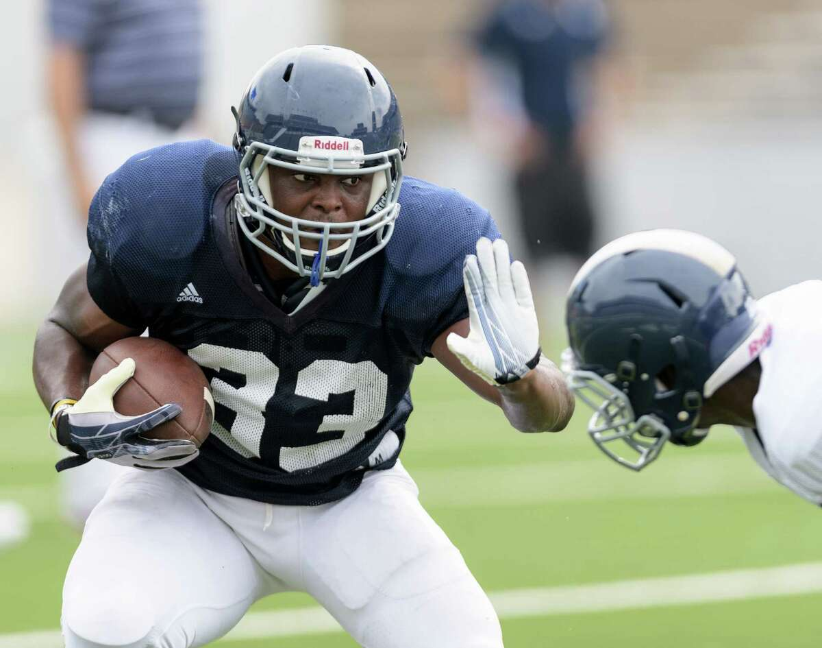 Emmanuel Esukpa (33) of the Rice Owls attempts to stiff arm a Rice defensive player in an inter squad scrimmage on Saturday, August 13, 2016 at Rice Stadium in Houston Texas.