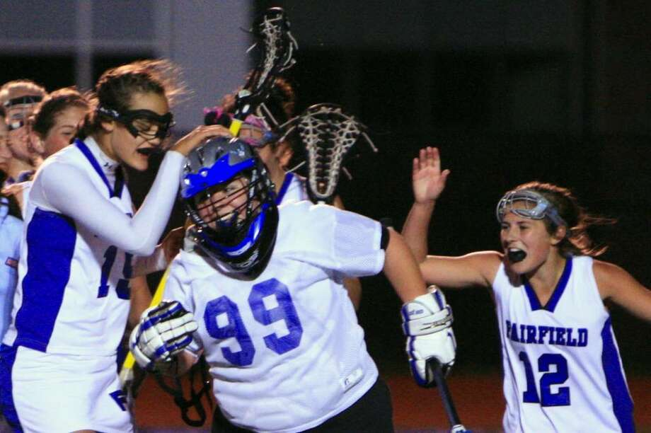 Fairfield Ludlowe's team celebrates around goalie Jill Moffett at the end of Ludlowe's 13-12 win over Staples in overtime on Tuesday. The Falcons have had reason to celebrate thus far this year as Ludlowe is off to a 6-1 start which is the best start in school history. Photo: Steve Stearns, Steve Stearns For The Fairfield Citizen