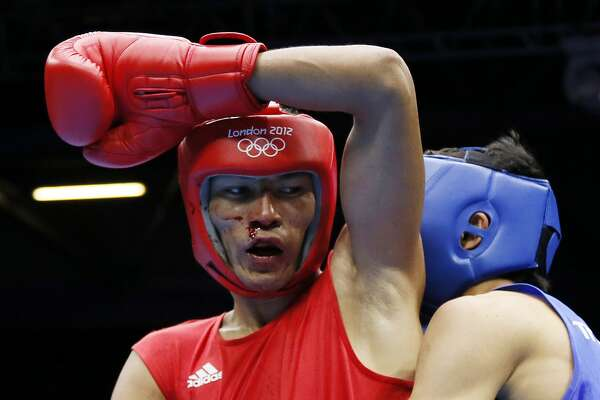 2012:  A bloodied Gani Zhailauov of Kazakhstan defends against Saylom Ardee of Thailand during their first round Lightweight (60Kg) match of the  London 2012 Olymipic Games at the Excel Arena in London.  Zhailauov won on a close points decision.