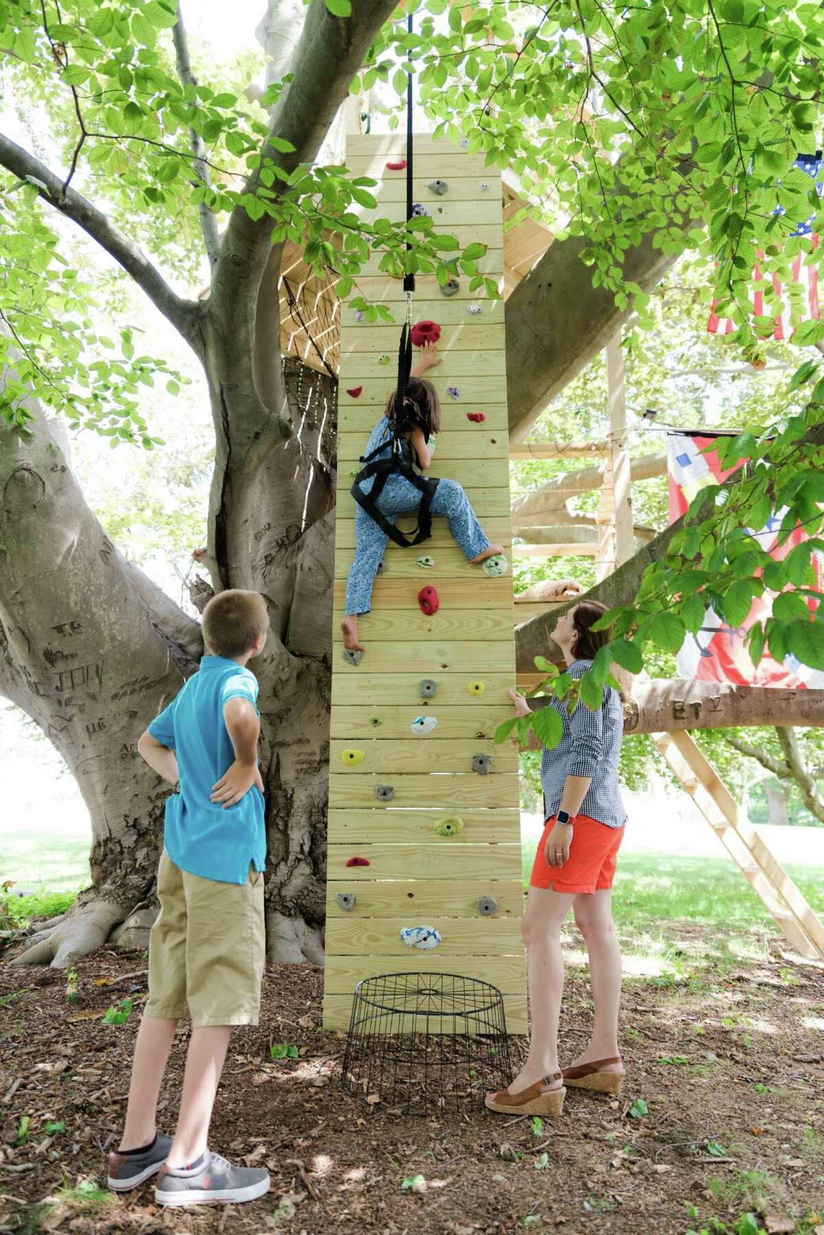 Rebecca Sikora safely ascends a climbing wall, an alternate way to get to the treehouse's top deck, as her brother James and their mother Ashley watch.