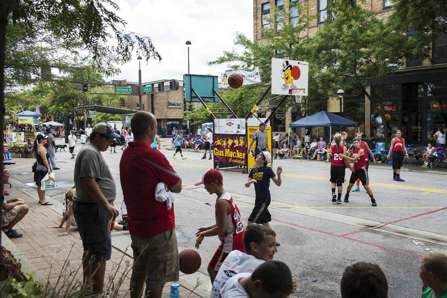 Participants in the third annual Gus Macker 3-on-3 basketball tournament compete along Main Street in downtown Midland on Saturday. Photo: THEOPHIL SYSLO ,  For The Daily News