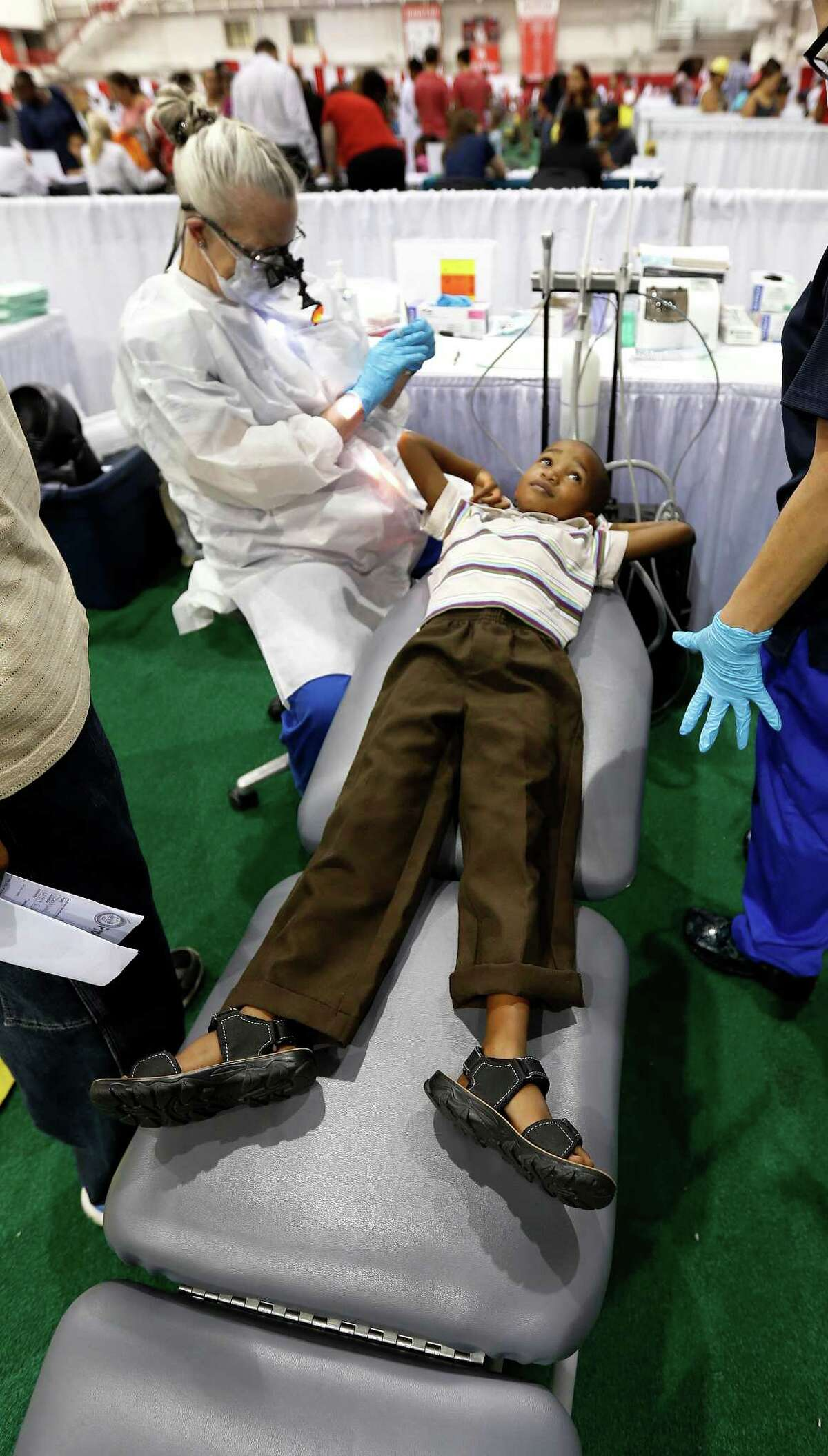 Isaac Mlambo, 6, gets his teeth checked by Johanna DeYoung, Bureau Chief for Oral Health with the City of Houston's Health Department, during the 6th Annual Mayor's Back 2 School Fest.