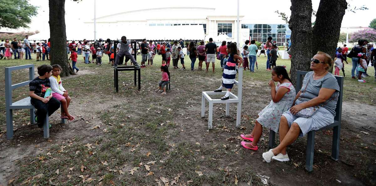 People sit in metal art chairs as the line of people waiting to get into the 6th Annual Mayor's Back 2 School Fest wrapped around the park area a couple of times.
