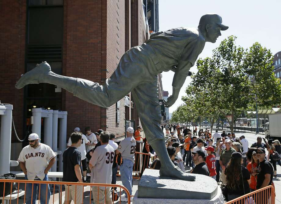 Fans wait to enter AT&T Park beneath a new statue of Hall of Fame pitcher Gaylord Perry before a baseball game between the San Francisco Giants and the Baltimore Orioles Saturday, Aug. 13, 2016, in San Francisco. The Giants unveiled the statue in a ceremony on Saturday. (AP Photo/Eric Risberg) Photo: Eric Risberg, Associated Press