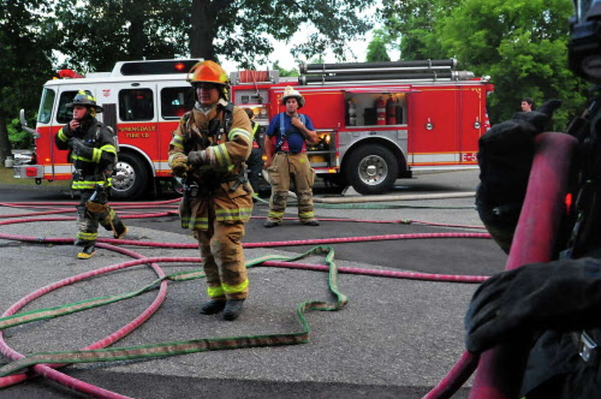 Volunteer firefighter recruits from Stamford train in a variety of firefighting techniques inside and outside of the fire training facility behind the Darien Town Yard in Darien, Conn., on Thursday Aug. 6, 2015. Some of the drills included hose line advancement practice into a simulated fire as well as search and rescue operations.