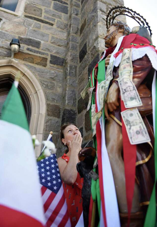Anna Gallo, of Glenville, kisses her hand after pinning money to the statue of St. Roch before the annual St. Roch Church procession through the streets in the Chickahominy section of Greenwich, Conn. Sunday, Aug. 14, 2016. To close out the Feast, the church paid tribute to St. Roch with a procession led by the Dixie Dandies band and a statue of St. Roch. Onlookers crowded the streets and pinned money to ribbons on the statue as the procession made its way through town. Photo: Tyler Sizemore / Hearst Connecticut Media / Greenwich Time