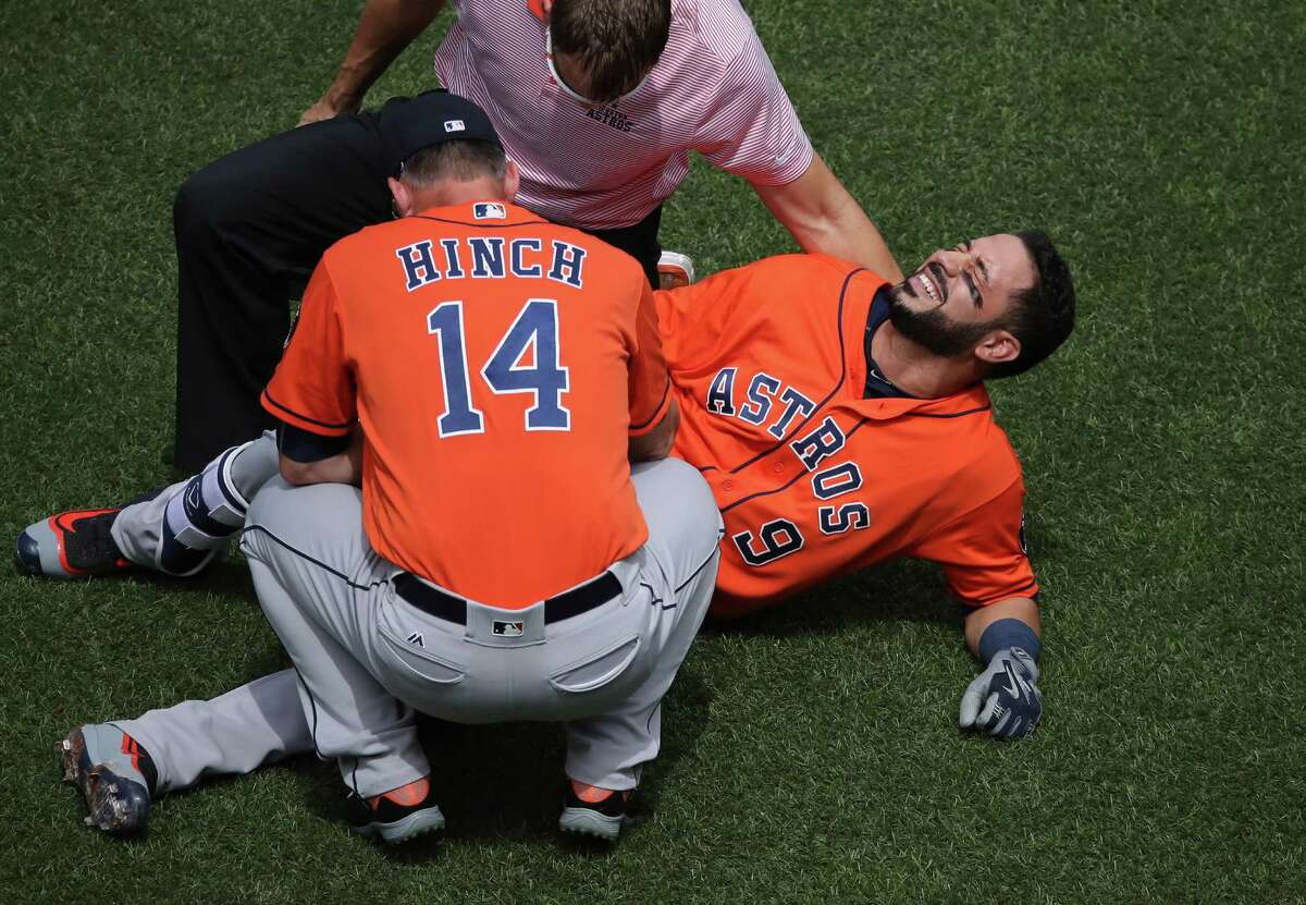 TORONTO, CANADA - AUGUST 14: Marwin Gonzalez #9 of the Houston Astros reacts after being hit by pitch as manager A.J. Hinch #14 and the trainer tend to him in the first inning during MLB game action against the Toronto Blue Jays on August 14, 2016 at Rogers Centre in Toronto, Ontario, Canada.