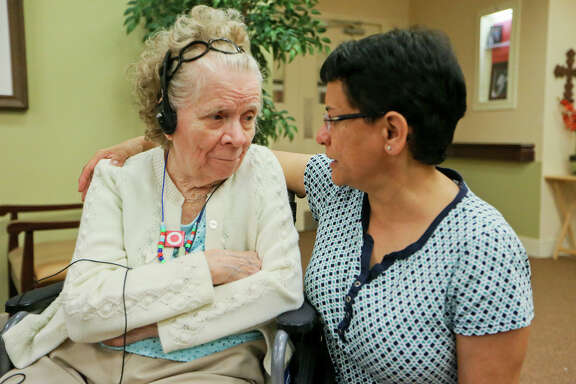 """Elsie Ramirez (left), 93, a resident at Franklin Park, listens to her favorite music on an iPod during a vieit by her daughter, Deanna Ramirez,at the senior living facility at 21802 Encino Commons on Monday, July 18, 2016. The iPod therapy is part of Franklin Park's """"Refreshing Waters"""" program utilizing music therapy in an attempt to find things residents in memory care used to do and incorporate it into their everyday life. MARVIN PFEIFFER/ mpfeiffer@express-news.net"""