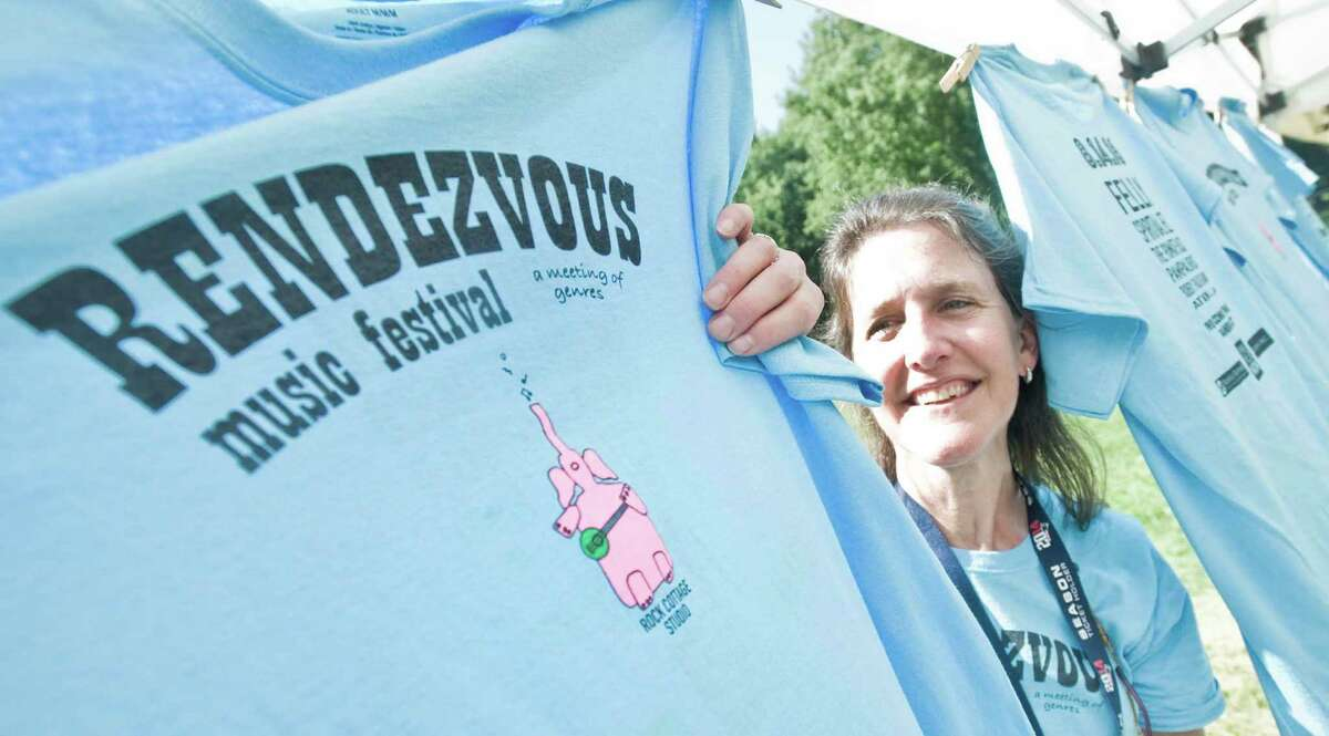 Tracy Sennett of Redding sells Rendezvous T-shirst at the music festival held at Ives Concert Park in Danbury. Sunday, Aug.14, 2016
