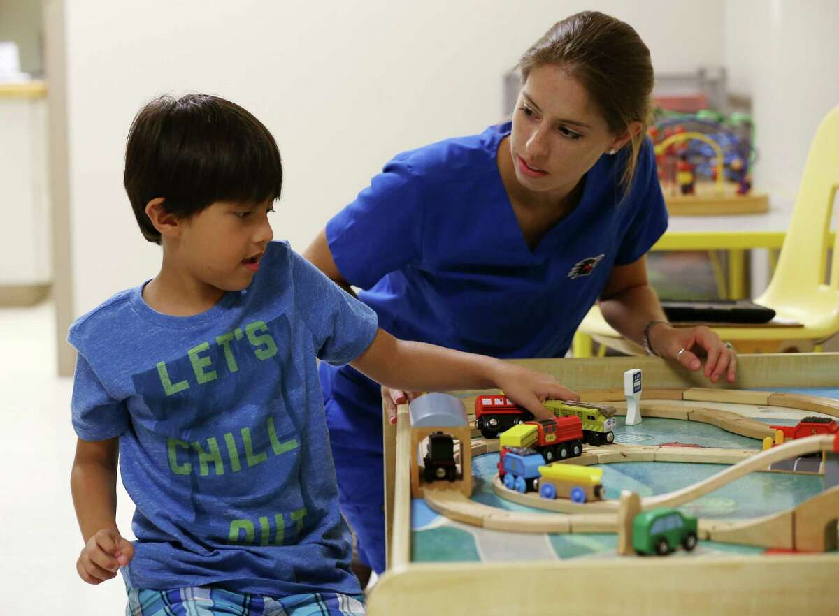 Registered Behavior Technician Elaina Garcia (right) works with Gael Gonzalez, 6, on communication and social skills at an autism clinic in the Goldsbury Center for Children and Families at the Children's Hospital of San Antonio on Aug. 9. The hospital along with the University of Texas at San Antonio and the Autism Treatment Center partnered to form the San Antonio Applied Behavior Analysis Project. The project aims to provide easy access to top-tier applied behavior analysis services to individuals with autism and developmental disabilities in the San Antonio area. It targets low-income families and will also train future providers.