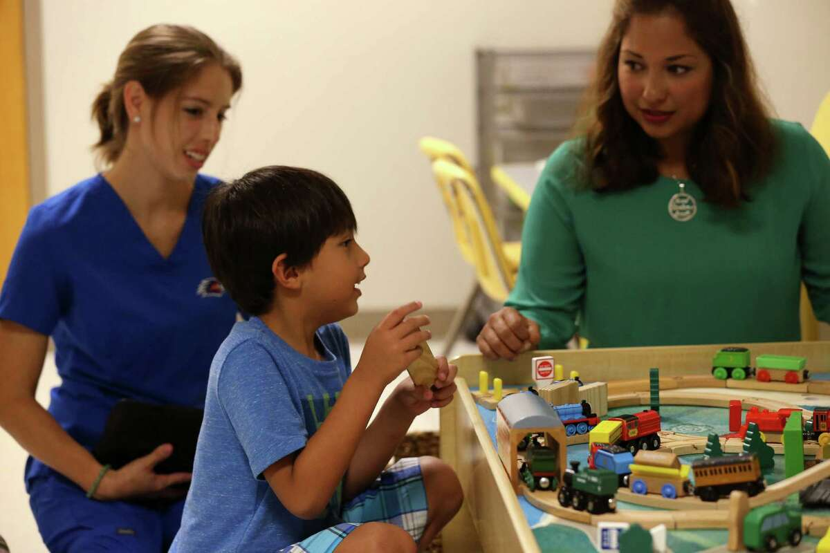 Gael Gonzalez, 6, plays with a train set in an exercise designed to improve his communications and social skills at an autism clinic in the Goldsbury Center for Children and Families at the Children's Hospital of San Antonio on Aug. 9. His mother, Marcela Gonzalez (right) also participates in the game along with registered Behavior Therapist Elaina Garcia.