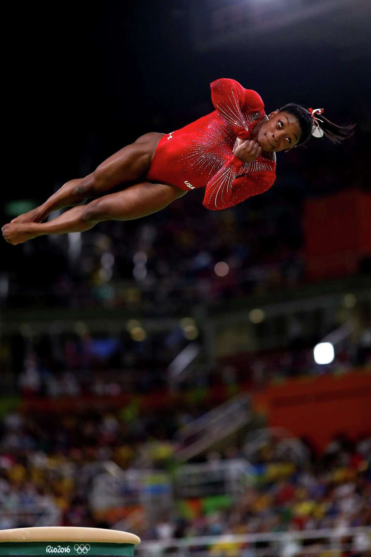 Spring's Simone Biles soars above the apparatus - and the other gymnasts - as she competes in the vault Sunday en route to winning the gold medal over Russia's Maria Paseka.