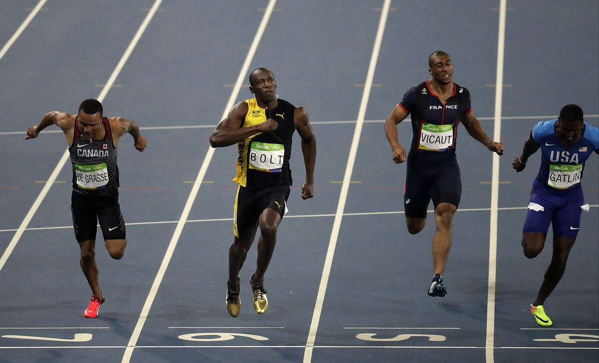Jamaica's Usain Bolt, second from left, celebrates as he crosses the line to win gold in the men's 100-meter final during the athletics competitions of the 2016 Summer Olympics at the Olympic stadium in Rio de Janeiro, Brazil, Sunday, Aug. 14, 2016. (AP Photo/Julio Cortez)