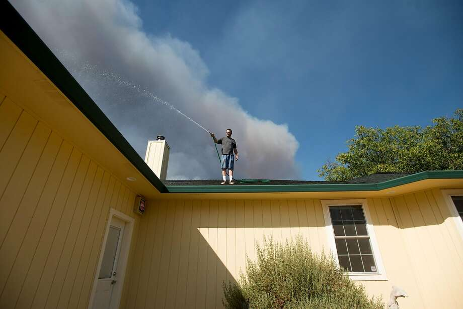 Ric Davis, who stayed to save his home despite a mandatory evacuation order, sprays water on his Morgan Valley Road home as the Clayton Fire approaches in Lower Lake, Calif., on Sunday, Aug. 14, 2016. Photo: Noah Berger, Special To The Chronicle