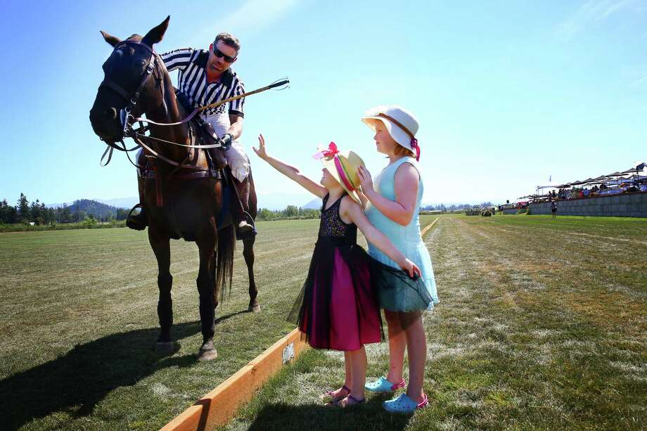 Addie Sparks, 8, and her sister Rory, 5, ask to pet Reno, ridden by tournament umpire Todd Randall, during a Polo Party hosted by Seattle Polo & Equestrian Club in Enumclaw, Sunday, Aug. 14, 2016.  Wearing their best hats and garden party attire, attendees gathered to watch polo matches, picnic, divot stomp, and socialize. Photo: GENNA MARTIN, SEATTLEPI.COM / SEATTLEPI.COM