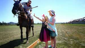 Addie Sparks, 8, and her sister Rory, 5, ask to pet Reno, ridden by tournament umpire Todd Randall, during a Polo Party hosted by Seattle Polo & Equestrian Club in Enumclaw, Sunday, Aug. 14, 2016.  Wearing their best hats and garden party attire, attendees gathered to watch polo matches, picnic, divot stomp, and socialize.