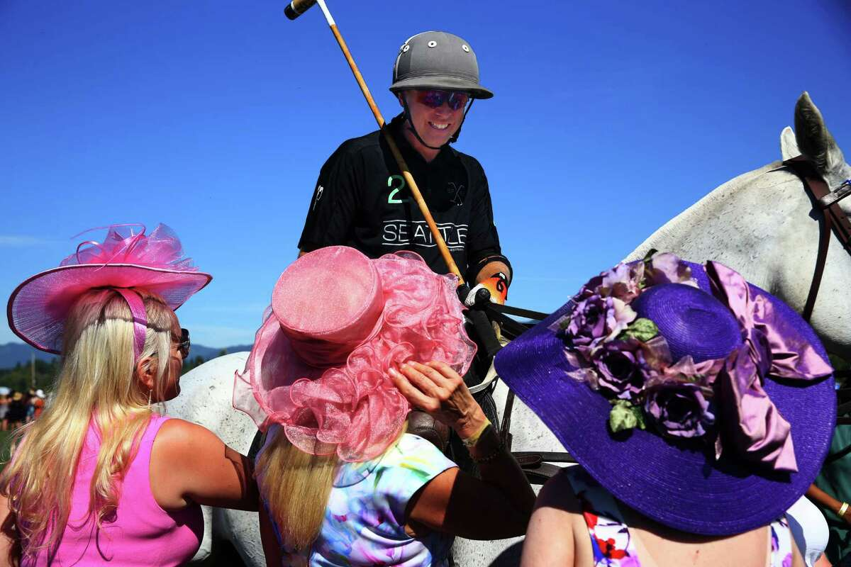 Seattle Polo Club player Cameron Smith talks with women in festive hats at half time during a Polo Party hosted by Seattle Polo & Equestrian Club in Enumclaw, Sunday, Aug. 14, 2016. Wearing their best hats and garden party attire, attendees gathered to watch polo matches, picnic, divot stomp, and socialize.