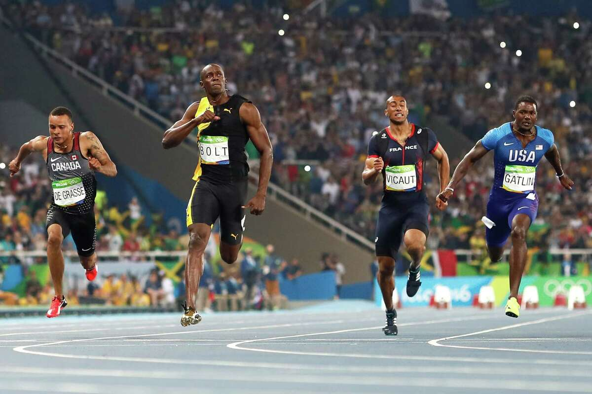 Usain Bolt, second from left, celebrates as he crosses the finish line to win the men's 100 meters ahead of Andre de Grasse, left; Jimmy Vicaut, second from right; and runner-up Justin Gatlin, far right.