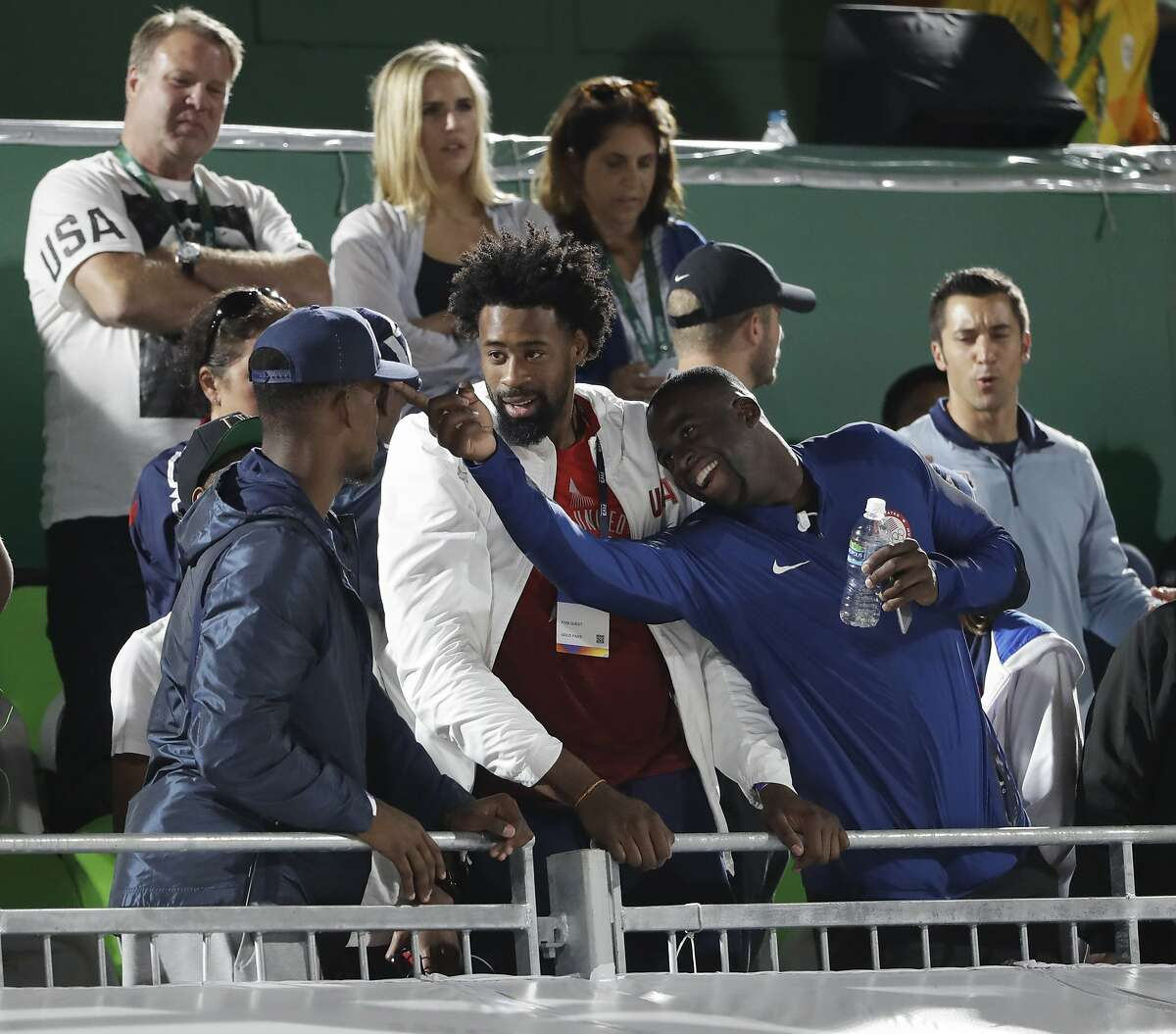 Members of the men's basketball team Jimmy Butler, from left, DeAndre Jordan and Draymond Green, of the United States, attend a women's beach volleyball quarterfinal match between Brazil and Russia at the 2016 Summer Olympics in Rio de Janeiro, Brazil, Sunday, Aug. 14, 2016. (AP Photo/Marcio Jose Sanchez)