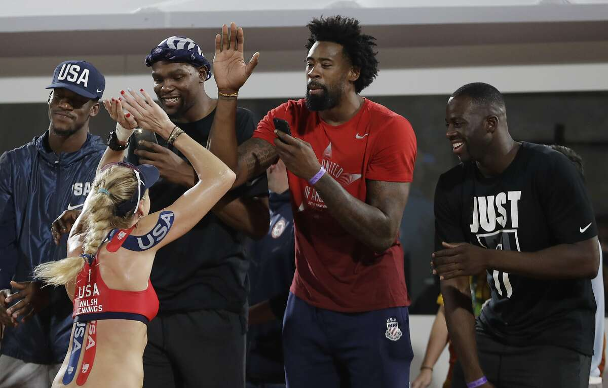 United States' Kerri Walsh Jennings celebrates with members of United States' basketball team, from left, Jimmy Butler, Kevin Durant, DeAndre Jordan and Draymond Green after winning a women's beach volleyball quarterfinal match against Australia at the 2016 Summer Olympics in Rio de Janeiro, Brazil, Monday, Aug. 15, 2016. (AP Photo/Petr David Josek)
