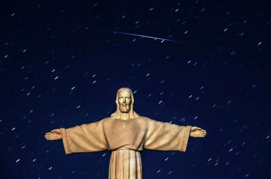 A Perseid meteor crosses the night sky over a statue of Jesus Christ in the village of Ivye some 125 km west of Minsk, on early August 13, 2016. To put one's hope in Him, then, is to believe despite all the evidence to the contrary Jesus' way of peace, justice, mercy and compassion will ultimately prevail over the empire's ways of violence, exploitation, oppression and fea  / AFP PHOTO / SERGEI GAPONSERGEI GAPON/AFP/Getty Images Photo: SERGEI GAPON, AFP/Getty Images / AFP or licensors