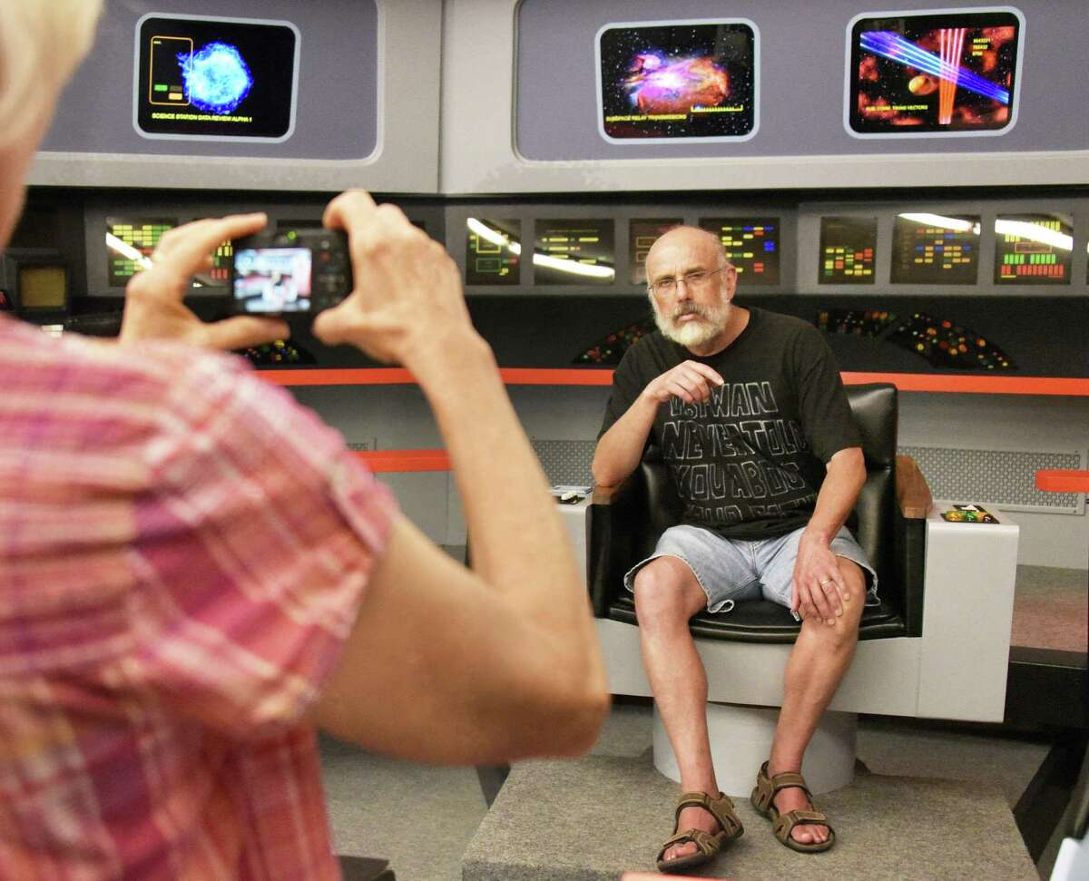 """Fan Mike Wilson ofHinesburg, Vt., affects his best Capt. Kirk pose as his wife Lori photographs him on the original Star Trek bridge during the second annual Star Trek & Nostalgia Convention - called """"Trekonderoga,"""" Friday Aug. 12, 2016 in Ticonderoga, NY. (John Carl D'Annibale / Times Union)"""