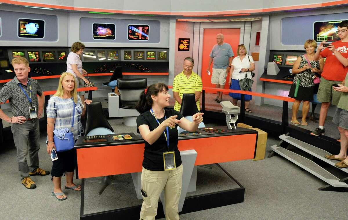 "Tour guide Marybeth Ritkouski, center, leads a group through a replica of the original Star Trek bridge during the second annual Star Trek & Nostalgia Convention - called ""Trekonderoga?"", Friday Aug. 12, 2016 in Ticonderoga, NY. (John Carl D'Annibale / Times Union)"