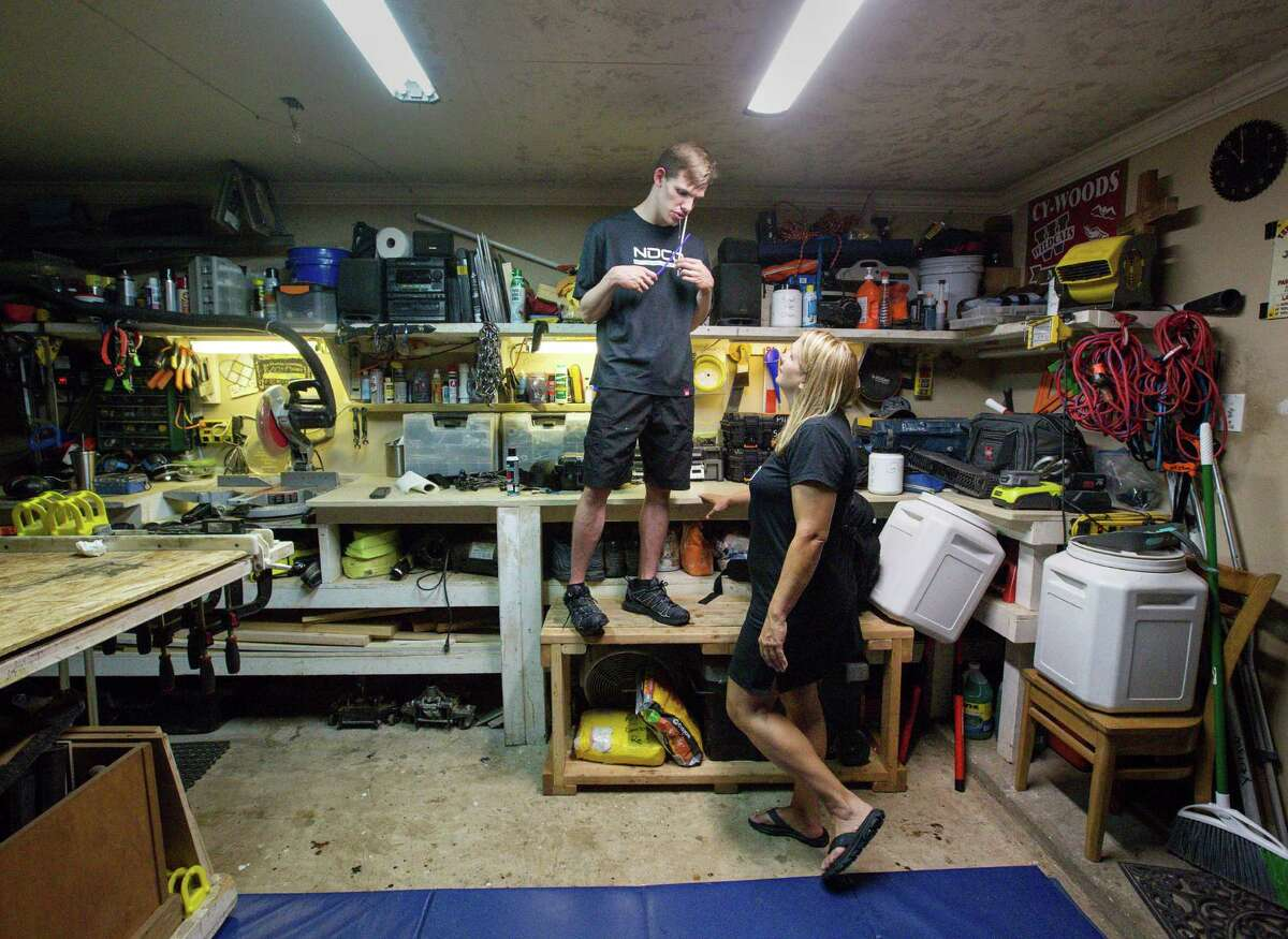 """Michelle Guppy talks to her 22-year-old autistic son Brandon as he climbs on a workbench in their garage in order to place his ear on a speaker playing music, Friday, Aug. 12, 2016, in Houston. Guppy says her son developed autism after receiving a vaccine when he was about 18 months old. She and her husband, Todd, have placed pads throughout their house because Brandon will fall when climbing on furniture and other things. """"We've heard that sound of him falling to the floor so many times it just sets us off,"""" she said."""