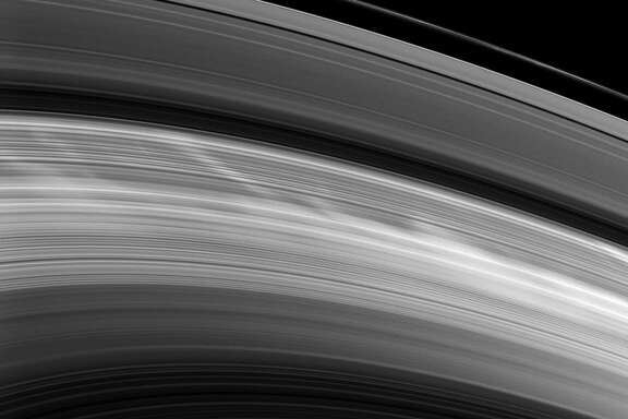 """The """"spokes"""" in Saturn's rings -- visible above as light ghostlike impressions -- were first discovered in the mid-1970s and first photographed by the Voyager spacecraft that buzzed by Saturn in the early 1980s."""