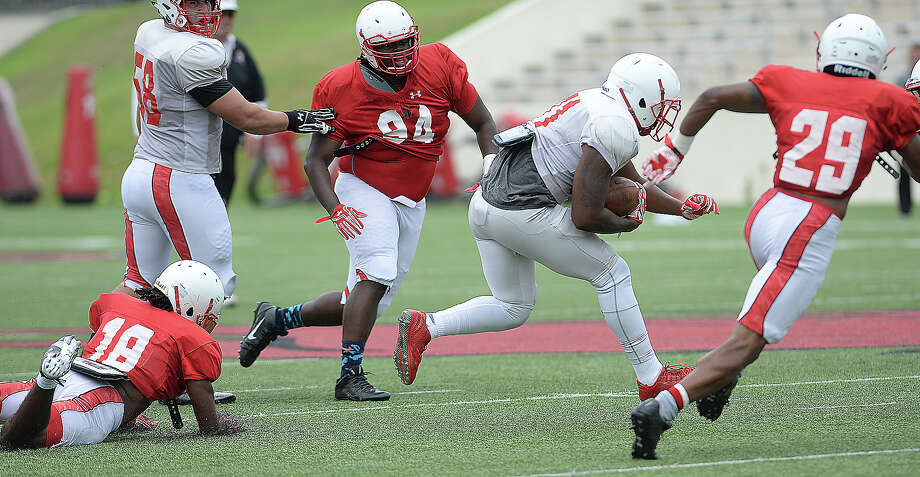 Lamar's #31 finds an opening to run the play as the offense and defense grapple on field during their first fall season scrimmage Saturday. Photo taken Saturday, August 13, 2016 Kim Brent/The Enterprise Photo: Kim Brent / Beaumont Enterprise