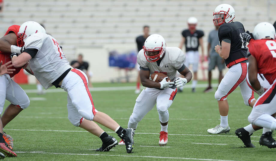 Lamar's Markell Hawthorne finds an opening to run the play as the offense and defense grapple on field during their first fall season scrimmage Saturday. Photo taken Saturday, August 13, 2016 Kim Brent/The Enterprise Photo: Kim Brent / Beaumont Enterprise