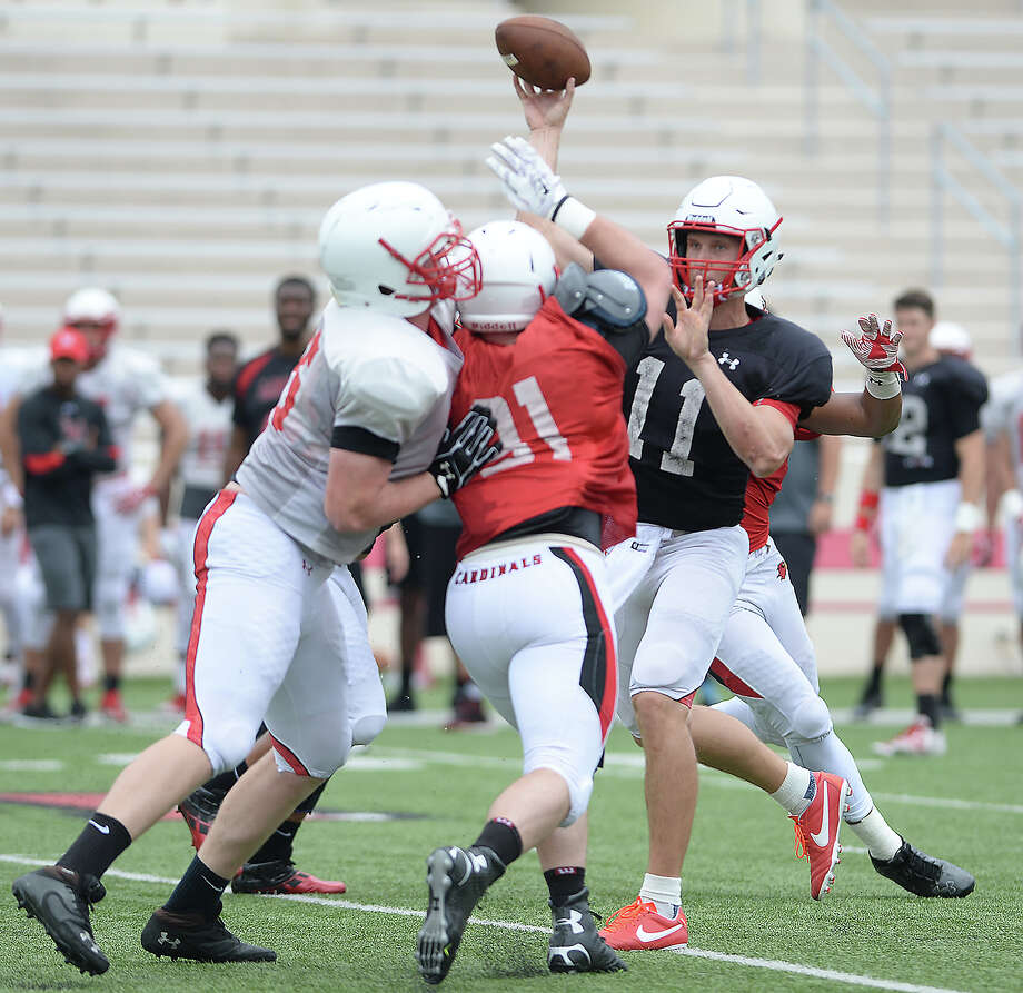 Lamar's Carson Earp passes as the offense and defense grapple on field during their first fall season scrimmage Saturday. Photo taken Saturday, August 13, 2016 Kim Brent/The Enterprise Photo: Kim Brent / Beaumont Enterprise