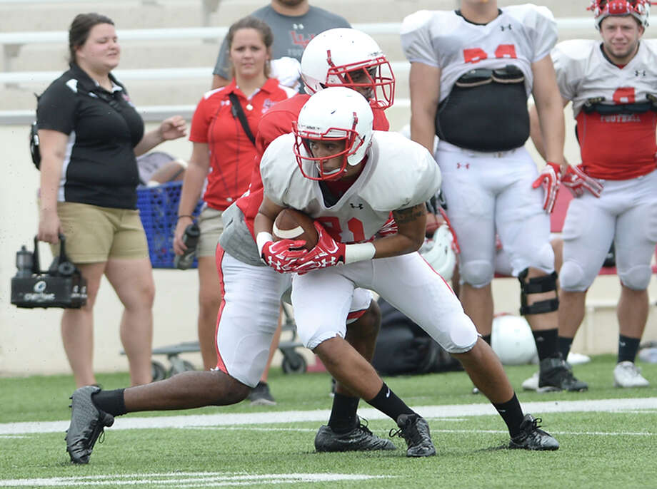 Lamar's Shane Hudson is tackled as he runs the ball as the offense and defense grapple on field during their first fall season scrimmage Saturday. Photo taken Saturday, August 13, 2016 Kim Brent/The Enterprise Photo: Kim Brent / Beaumont Enterprise