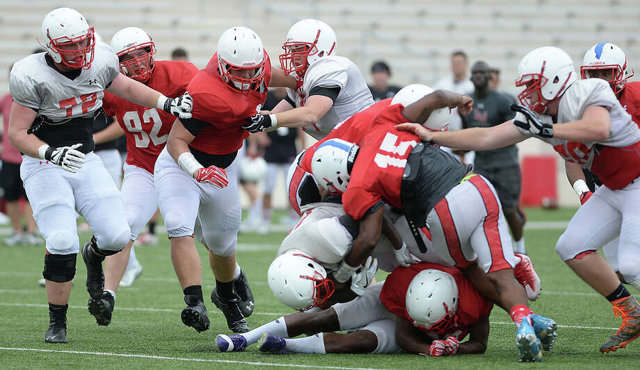 Lamar's offense and defense grapple on field during their first fall season scrimmage Saturday. Photo taken Saturday, August 13, 2016 Kim Brent/The Enterprise Photo: Kim Brent / Beaumont Enterprise